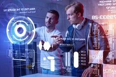 Σοβαροί συνάδελφοι που φαίνονται συγκεντρωμένοι εξεταστικοί ένα νέο σύστημα ασφαλείας Στοκ Εικόνες