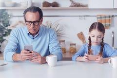 Σοβαροί όμορφοι πατέρας και κόρη που χρησιμοποιούν τα smartphones τους Στοκ Φωτογραφία