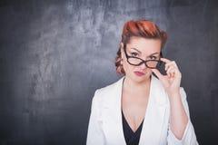 Σοβαρός δάσκαλος στα γυαλιά στο υπόβαθρο πινάκων Στοκ φωτογραφία με δικαίωμα ελεύθερης χρήσης