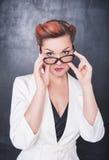Σοβαρός δάσκαλος στα γυαλιά στο υπόβαθρο πινάκων Στοκ Εικόνα