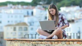 Σοβαρός έφηβος που γράφει σε ένα lap-top στις διακοπές απόθεμα βίντεο