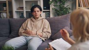 Σοβαρός έφηβος που περνά τη δοκιμή ψυχολογίας ενώ γιατρός που υποβάλλει τις ερωτήσεις απόθεμα βίντεο
