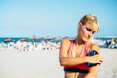 Σοβαρός αθλητής που βάζει armband για το τηλέφωνο Στοκ Φωτογραφίες