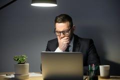 Σοβαρός αμφισβητήσιμος επιχειρηματίας που εξετάζει το lap-top, τη σκέψη και το κολλοειδές διάλυμα Στοκ εικόνα με δικαίωμα ελεύθερης χρήσης