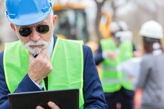 Σοβαρός, ανησυχημένος, ανώτερος γκρίζος μαλλιαρός μηχανικός ή επιχειρηματίας που εργάζεται σε μια ταμπλέτα στο εργοτάξιο οικοδομή στοκ φωτογραφίες με δικαίωμα ελεύθερης χρήσης