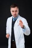 Σοβαρός αρσενικός γιατρός που δείχνει στη κάμερα στο μαύρο υπόβαθρο Στοκ φωτογραφία με δικαίωμα ελεύθερης χρήσης