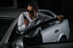 σοβαρός αρσενικός μυστικός αξιωματούχος στα γυαλιά ηλίου που χρησιμοποιούν την ομιλούσα ταινία walkie στοκ εικόνα