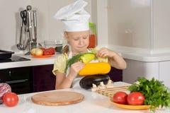Σοβαρός αρχιμάγειρας παιδιών που συσσωρεύει το φρέσκο λαχανικό Στοκ Φωτογραφία