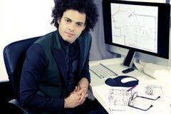 Σοβαρός αρχιτέκτονας που εργάζεται με τον υπολογιστή στο γραφείο που φαίνεται κάμερα Στοκ Φωτογραφία