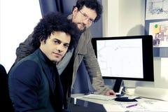 Σοβαρός αρχιτέκτονας που εργάζεται με τον υπολογιστή στο γραφείο που φαίνεται κάμερα Στοκ εικόνες με δικαίωμα ελεύθερης χρήσης
