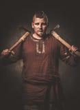 Σοβαρός Βίκινγκ με τους άξονες ενδύματα στα παραδοσιακά πολεμιστών, που θέτουν σε ένα σκοτεινό υπόβαθρο Στοκ Εικόνες