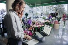 Σοβαρός βοηθός καταστημάτων που μιλά ανά τηλέφωνο με το συνεργάτη στοκ φωτογραφία
