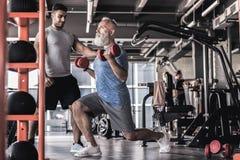 Σοβαρός γενειοφόρος αρσενικός χρόνος εξόδων στην αθλητική λέσχη με τον εκπαιδευτή Στοκ φωτογραφίες με δικαίωμα ελεύθερης χρήσης