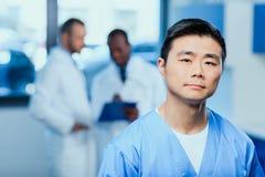 Σοβαρός γιατρός ιατρικό σε ομοιόμορφο με τους συναδέλφους πίσω στην κλινική Στοκ Φωτογραφίες