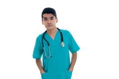 Σοβαρός γιατρός νεαρών άνδρων μπλε σε ομοιόμορφο με το stethoscop στο λαιμό του που θέτει και που εξετάζει τη κάμερα που απομονών Στοκ Εικόνες
