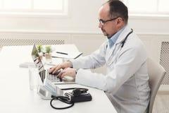 Σοβαρός γιατρός στα γυαλιά που δακτυλογραφεί στο lap-top Στοκ Εικόνα