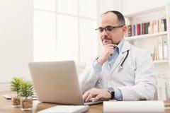 Σοβαρός γιατρός στα γυαλιά που δακτυλογραφεί στο lap-top Στοκ Εικόνες