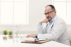 Σοβαρός γιατρός στα γυαλιά που δακτυλογραφεί στο lap-top Στοκ εικόνα με δικαίωμα ελεύθερης χρήσης