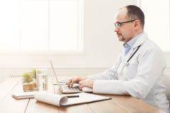 Σοβαρός γιατρός στα γυαλιά που κάθεται στον υπολογιστή γραφείου Στοκ φωτογραφίες με δικαίωμα ελεύθερης χρήσης