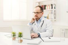 Σοβαρός γιατρός στα γυαλιά που κάθεται στον υπολογιστή γραφείου Στοκ φωτογραφία με δικαίωμα ελεύθερης χρήσης