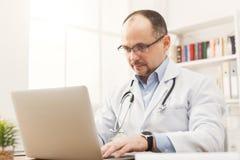 Σοβαρός γιατρός στα γυαλιά που κάθεται στον υπολογιστή γραφείου Στοκ Εικόνες