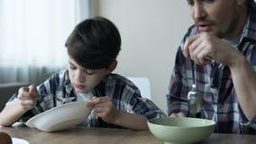 Σοβαρός ενιαίος πατέρας και ο γιος του που τρώνε τα δημητριακά το πρωί, φτωχό πρόγευμα απόθεμα βίντεο