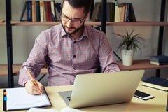 Σοβαρός επιχειρηματίας με τα γυαλιά που λειτουργούν στο γραφείο Στοκ Εικόνες