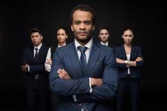 Σοβαρός επιχειρηματίας με τους επιχειρησιακούς συναδέλφους του που στέκονται με τα όπλα που διασχίζονται και που εξετάζουν τη κάμ Στοκ Εικόνα
