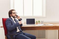 Σοβαρός επιχειρηματίας που διοργανώνει την τηλεφωνική συζήτηση Στοκ φωτογραφία με δικαίωμα ελεύθερης χρήσης