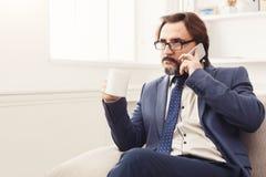 Σοβαρός επιχειρηματίας που διοργανώνει την τηλεφωνική συζήτηση Στοκ εικόνα με δικαίωμα ελεύθερης χρήσης