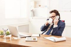 Σοβαρός επιχειρηματίας που διοργανώνει την τηλεφωνική συζήτηση Στοκ Εικόνα