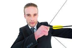Σοβαρός επιχειρηματίας που εξακοντίζει ένα τόξο και ένα βέλος Στοκ εικόνες με δικαίωμα ελεύθερης χρήσης