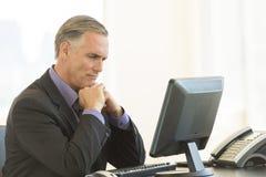 Σοβαρός επιχειρηματίας που εξετάζει τον προσωπικό υπολογιστή γραφείου στην αρχή Στοκ εικόνα με δικαίωμα ελεύθερης χρήσης