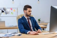 Σοβαρός επιχειρηματίας που εξετάζει τον υπολογιστή Στοκ Εικόνα