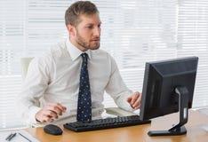 Σοβαρός επιχειρηματίας που εξετάζει τον υπολογιστή Στοκ Εικόνες