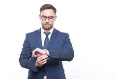 Σοβαρός επιχειρηματίας που εξετάζει το wristwatch του Στοκ εικόνα με δικαίωμα ελεύθερης χρήσης