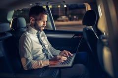 Σοβαρός επιχειρηματίας που εργάζεται αργά στο αυτοκίνητο στο lap-top στοκ εικόνα