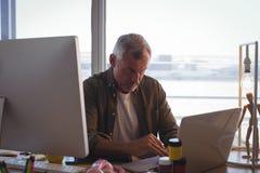 Σοβαρός επιχειρηματίας που εργάζεται στο lap-top στο γραφείο γραφείων Στοκ φωτογραφία με δικαίωμα ελεύθερης χρήσης