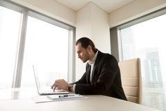Σοβαρός επιχειρηματίας που εργάζεται στο lap-top στο γραφείο στην αρχή Στοκ φωτογραφία με δικαίωμα ελεύθερης χρήσης