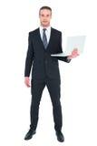 Σοβαρός επιχειρηματίας που θέτει και που κρατά το lap-top Στοκ Εικόνες