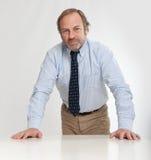 Σοβαρός επιχειρηματίας που κλίνει σε έναν πίνακα Στοκ Εικόνες