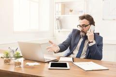 Σοβαρός επιχειρηματίας που μιλά στο κινητό τηλέφωνο Στοκ εικόνα με δικαίωμα ελεύθερης χρήσης