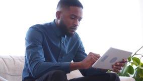 Σοβαρός επιχειρηματίας που χρησιμοποιεί την ψηφιακή ταμπλέτα στο γραφείο απόθεμα βίντεο