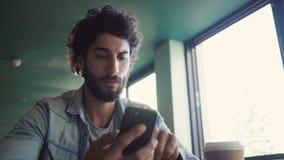 Σοβαρός επιχειρηματίας που χρησιμοποιεί το έξυπνο τηλέφωνο στον καφέ απόθεμα βίντεο