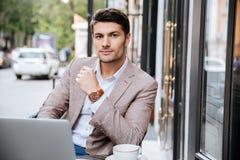 Σοβαρός επιχειρηματίας που χρησιμοποιεί το σύγχρονο lap-top στη καφετερία Στοκ Εικόνες