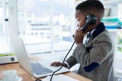 Σοβαρός επιχειρηματίας που χρησιμοποιεί το τηλέφωνο και το lap-top στο γραφείο Στοκ Εικόνα