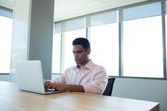 Σοβαρός επιχειρηματίας που χρησιμοποιεί το lap-top στη αίθουσα συνδιαλέξεων Στοκ Φωτογραφία