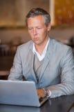 Σοβαρός επιχειρηματίας που χρησιμοποιεί το lap-top του Στοκ Εικόνες