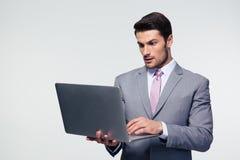 Σοβαρός επιχειρηματίας που χρησιμοποιεί το lap-top Στοκ Φωτογραφία