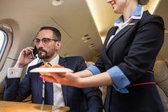 Σοβαρός επιχειρηματίας που χρησιμοποιεί privet το αεριωθούμενο αεροπλάνο στοκ εικόνα